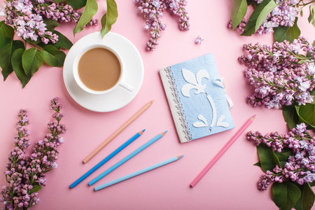 Purple lilac flowers and a cup of coffee  with notebook and colored pencils on pastel pink
