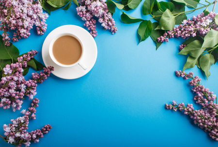 Purple lilac flowers and a cup of coffee on pastel blue Reklamní fotografie - 124156263
