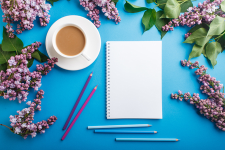 Purple lilac flowers and a cup of coffee with notebook and colored pencils on pastel blue Reklamní fotografie - 124156264