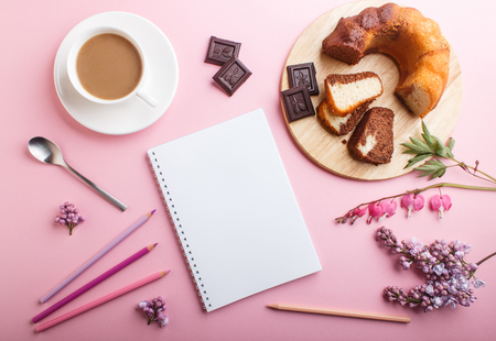 Purple lilac and bleeding heart  flowers and a cup of coffee with notebook, cake and colored pencils on pastel pink