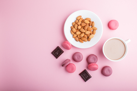 Purple and pink macaron or macaroon cakes with cup of coffee and almonds on pastel pink Reklamní fotografie - 124156269