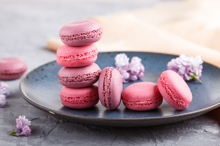 Purple and pink macaron or macaroon cakes with lilac flowers on blue ceramic plate on a gray concrete