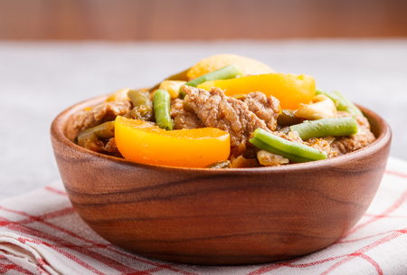 Fried pork with peaches, cashew and green beans in a wooden bowl on a gray concrete Reklamní fotografie - 124156274