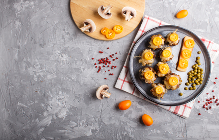 Stuffed fried champignons with cheese, kumquats and green peas on a gray concrete Reklamní fotografie - 124156275