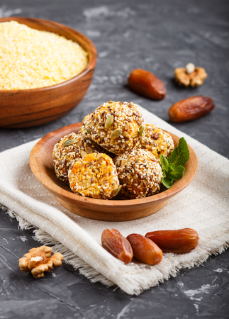 Energy ball cakes with dried apricots, sesame, cornflakes, linen, walnuts and dates with green mint leaves in a wooden bowl on a black concrete Reklamní fotografie - 124156246