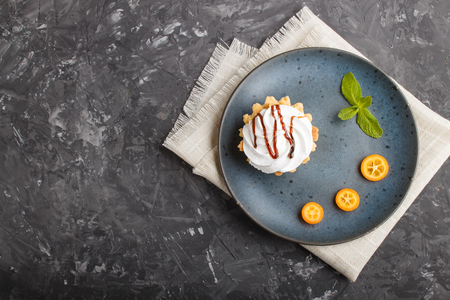 Cake with whipped egg cream on a blue ceramic plate with kumquat slices and mint leaves on a black concrete  with linen napkin. Reklamní fotografie - 124156245