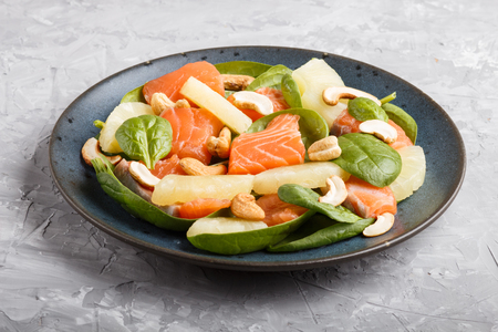 Fresh salmon with pineapple, spinach and cashew  on a gray concrete Reklamní fotografie - 124156247