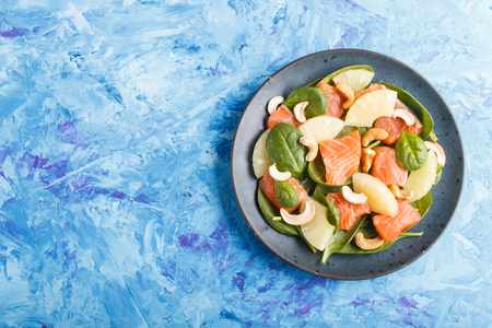 Fresh salmon with pineapple, spinach and cashew  on a blue concrete