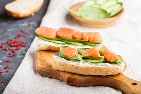 Smoked salmon sandwiches with cucumber and spinach on wooden board on a linen Reklamní fotografie - 124156249