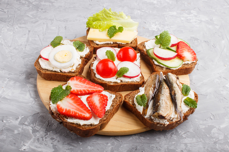 Set of different sandwiches with cheese, radish, lettuce, strawberry, sprats, tomatoes and cucumber on wooden board on a gray concrete Reklamní fotografie - 124156255