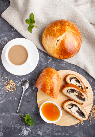 Homemade yeast buns and rolls with poppy seeds and honey on a black concrete background with a cup of coffee. top view, flat lay. Reklamní fotografie - 124156259
