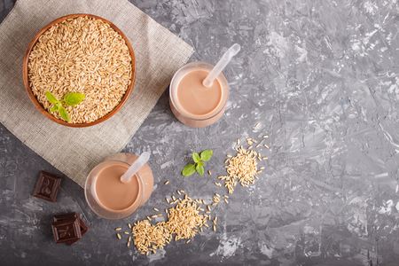 Organic non dairy oat chocolate milk in glass and wooden plate with oat seeds on a gray concrete background. Vegan healthy food concept, flat lay, top view, copy space. Reklamní fotografie - 124400654