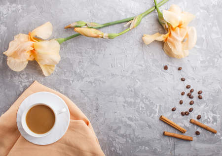 Orange iris flowers and a cup of coffee on a gray concrete background. Morninig, spring, fashion composition. Flat lay, top view, copy space. Reklamní fotografie - 124400663