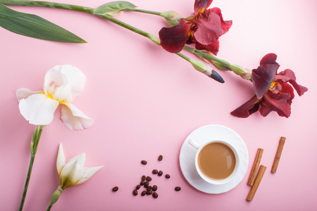 White and burgundy iris flowers and a cup of coffee on pastel pink background. Morninig, spring, fashion composition. Flat lay, top view, copy space. Reklamní fotografie - 124400669