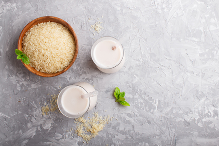 Organic non dairy rice milk in glass and wooden plate with rice seeds on a gray concrete background. Vegan healthy food concept, flat lay, top view, copy space. Reklamní fotografie - 124400672