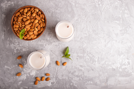Organic non dairy almond milk in glass and wooden plate with almond nuts on a gray concrete background. Vegan healthy food concept, flat lay, top view, copy space. Reklamní fotografie - 124399415