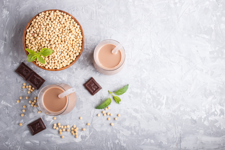 Organic non dairy soy chocolate milk in glass and wooden plate with soybeans on a gray concrete background. Vegan healthy food concept, flat lay, top view, copy space. Reklamní fotografie - 124399422
