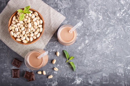 Organic non dairy pistachio milk in glass and wooden plate with pistachionuts on a black concrete background. Vegan healthy food concept, flat lay, top view, copy space. Reklamní fotografie - 124399424