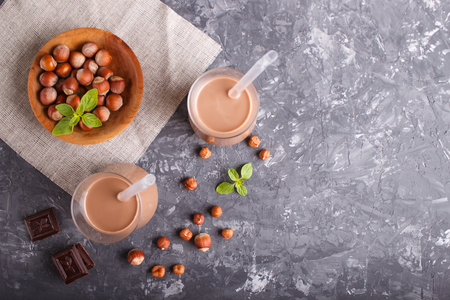 Organic non dairy hazelnut chocolate milk in glass and wooden plate with hazelnuts on a gray concrete background. Vegan healthy food concept, flat lay, top view, copy space. Reklamní fotografie - 124399426