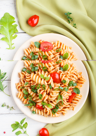 Fusilli pasta with tomato sauce, cherry tomatoes, lettuce and herbs on a white wooden background with green textile. top view, flat lay, copy space. Reklamní fotografie - 124399431