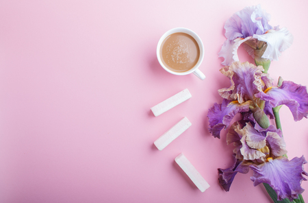 Purple iris flowers and a cup of coffee on pastel pink background. Morninig, spring, fashion composition. Flat lay, top view, copy space. Reklamní fotografie - 124399436