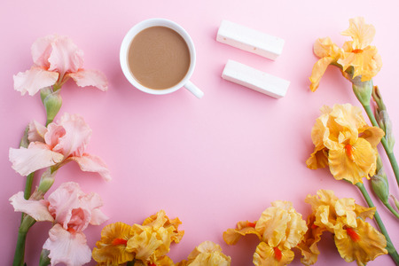 Pink and orange iris flowers and a cup of coffee on pastel pink background. Morninig, spring, fashion composition. Flat lay, top view, copy space. Reklamní fotografie - 124399437