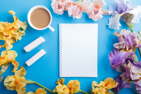 Purple, pink, yellow iris flowers and a cup of coffee with notebook on pastel blue background. Morninig, spring, fashion composition. Flat lay, top view. Reklamní fotografie - 124399447