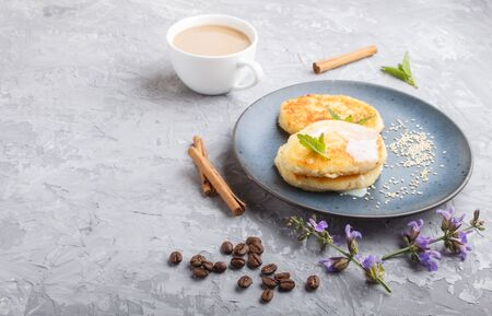 Cheese pancakes on a blue ceramic plate and a cup of coffee on a gray concrete background. side view, copy space.