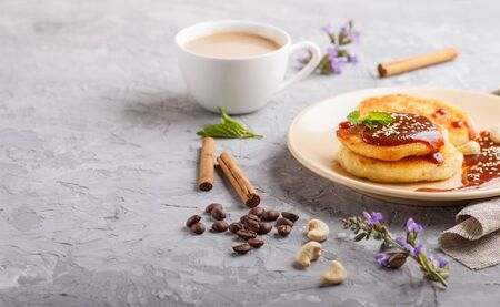 Cheese pancakes with caramel sauce on a beige ceramic plate and a cup of coffee on a gray concrete background. side view, close up.