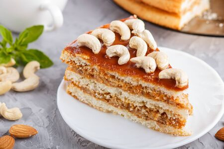 Piece of homemade cake with caramel cream and nuts with cup of coffee on a gray concrete  background. side view, close up, selective focus.