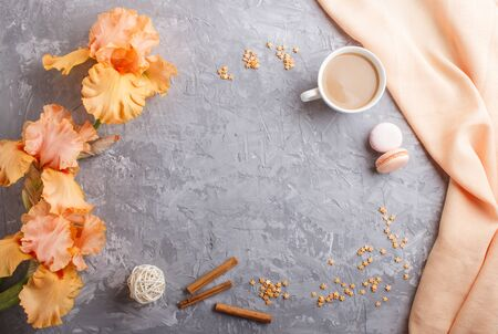 Orange iris flowers and a cup of coffee on a gray concrete background. Morninig, spring, fashion composition. Flat lay, top view, copy space. Reklamní fotografie - 124580118