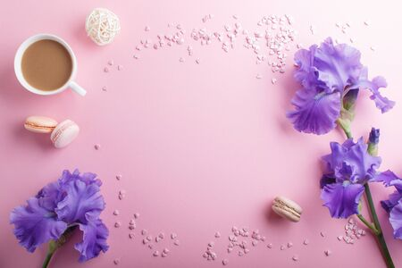 Purple iris flowers and a cup of coffee on a pink pastel background. Morninig, spring, fashion composition. Flat lay, top view, copy space. Reklamní fotografie - 124580121