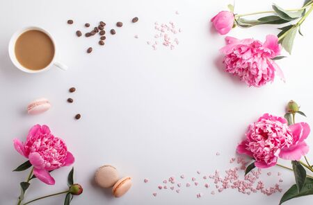 Pink peony flowers and a cup of coffee on a white background. Morninig, spring, fashion composition. Flat lay, top view, copy space. Reklamní fotografie - 124580123