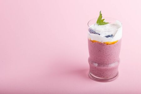 smoothie with honeysuckle, linen and chia in a glass on pink pastel background. side view, close up, copy space.