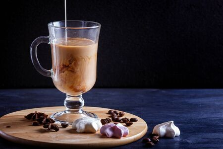 Glass cup of coffee with cream poured over and meringues on a wooden board on a black