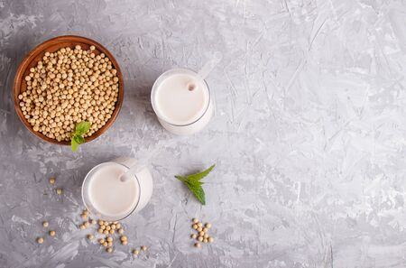 Organic non dairy soy milk in glass and wooden plate with soybeans on a gray concrete