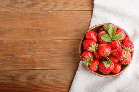Fresh red strawberry in wooden bowl on wooden