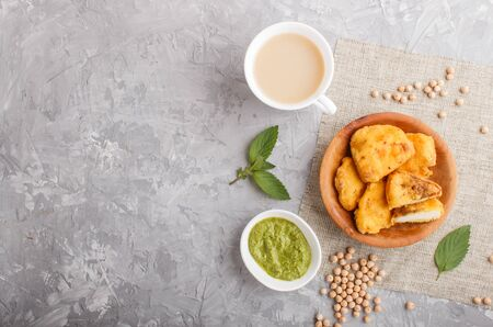 Traditional indian food paneer pakora in wooden plate with mint chutney on a gray concrete