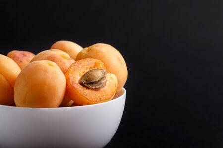 Frische orange Aprikosen in weißer Schüssel auf Schwarz