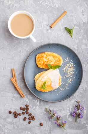 Cheese pancakes on a blue ceramic plate and a cup of coffee on a gray concrete background. top view, flat lay.