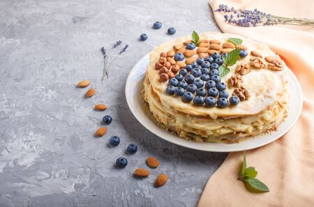 Homemade layered Napoleon cake with milk cream. Decorated with blueberry, almonds, walnuts, hazelnuts, mint on a gray concrete  background and orange textile. side view. copy space. Reklamní fotografie