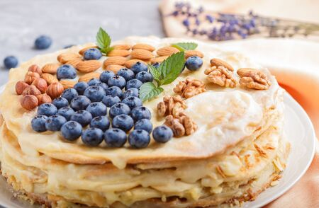 Homemade layered Napoleon cake with milk cream. Decorated with blueberry, almonds, walnuts, hazelnuts, mint on a gray concrete  background. side view, selective focus, close up. Reklamní fotografie