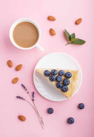 Homemade layered Napoleon cake with milk cream. Decorated with blueberry, almonds, mint on a pastel pink background and a cup of coffee. top view. flat lay, close up. Reklamní fotografie