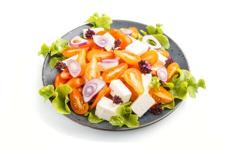 Vegetarian salad with fresh grape tomatoes, feta cheese, lettuce and onion on blue ceramic plate isolated on white background, side view, close up.
