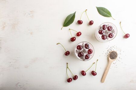 Yoghurt with cherries, chia seeds and granola in glass with wooden spoon on white wooden background. top view, copy space, flat lay. Reklamní fotografie