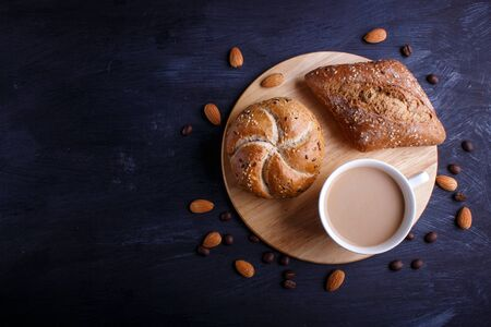 Cup of coffee with cream  and buns on a black background. top view, flat lay, copy space.