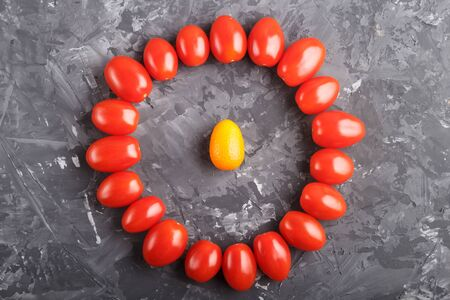 one kumquat in a circle of cherry tomatoes on a black concrete background, top view, contrast, opposition concept.