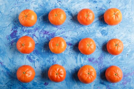 Rows of tangerines on a blue concrete background, top view, flat lay. Reklamní fotografie