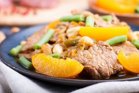 Fried pork with peaches, cashew and green beans on a black concrete background. Side view, close up, chinese cuisine, selective focus, macro. Reklamní fotografie