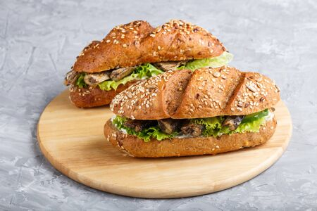 Sprats sandwiches with lettuce and cream cheese on wooden board on a gray concrete background. side view, close up.